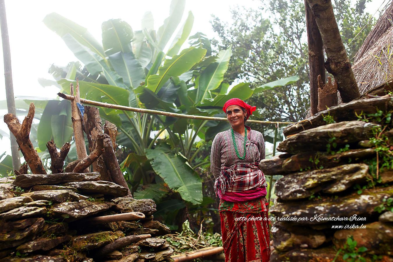 Femme souriante à l'entrée de sa maison